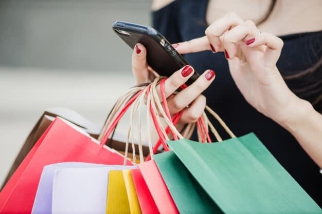 woman-with-shopping-bags-holding-smartphone_23-2147652180